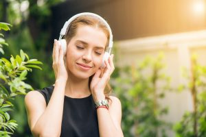 Woman listening to music through headphones outdoors