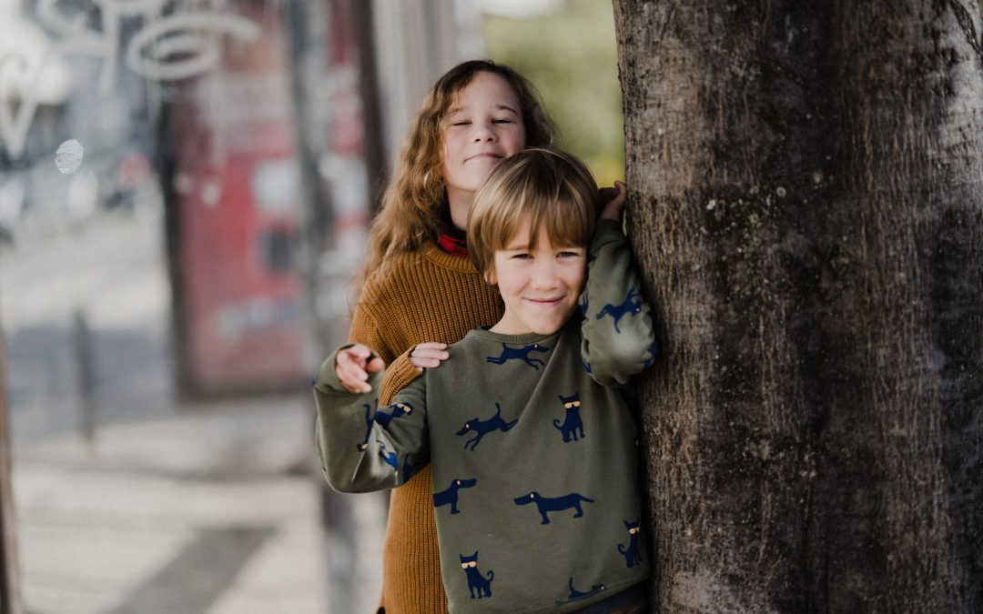 Brother and sister posing for photo beside a tree