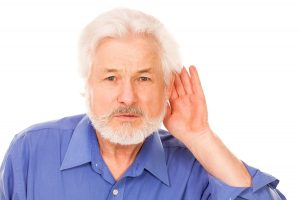 Handsome elderly man holds hand on ear isolated over white background