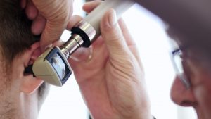 Close up of an audiologist performing a hearing test on a patient.