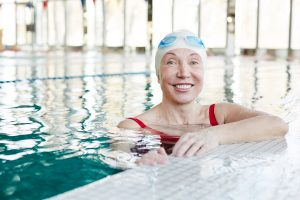 Happy and healthy senior female with toothy smile looking at you while spending leisure in swimming-pool