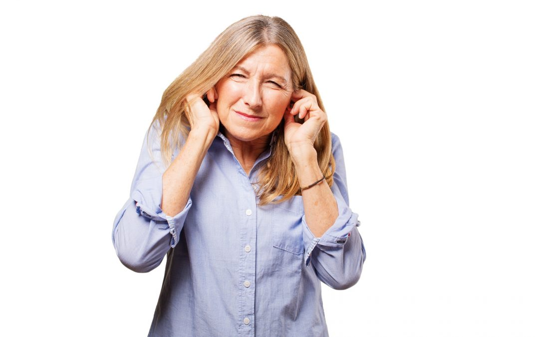 Senior woman covering her ears because of hearing aid feedback noise
