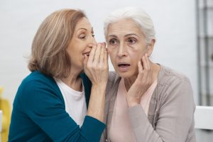 Senior woman with unilateral hearing loss being spoken to in strong ear