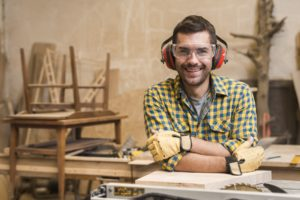 Male carpenter wearing ear protection to prevent hearing loss