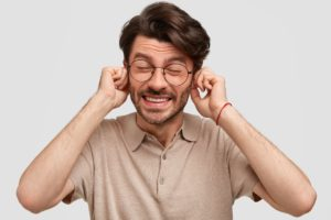 Photo of man suffering from tinnitus plugging his ears