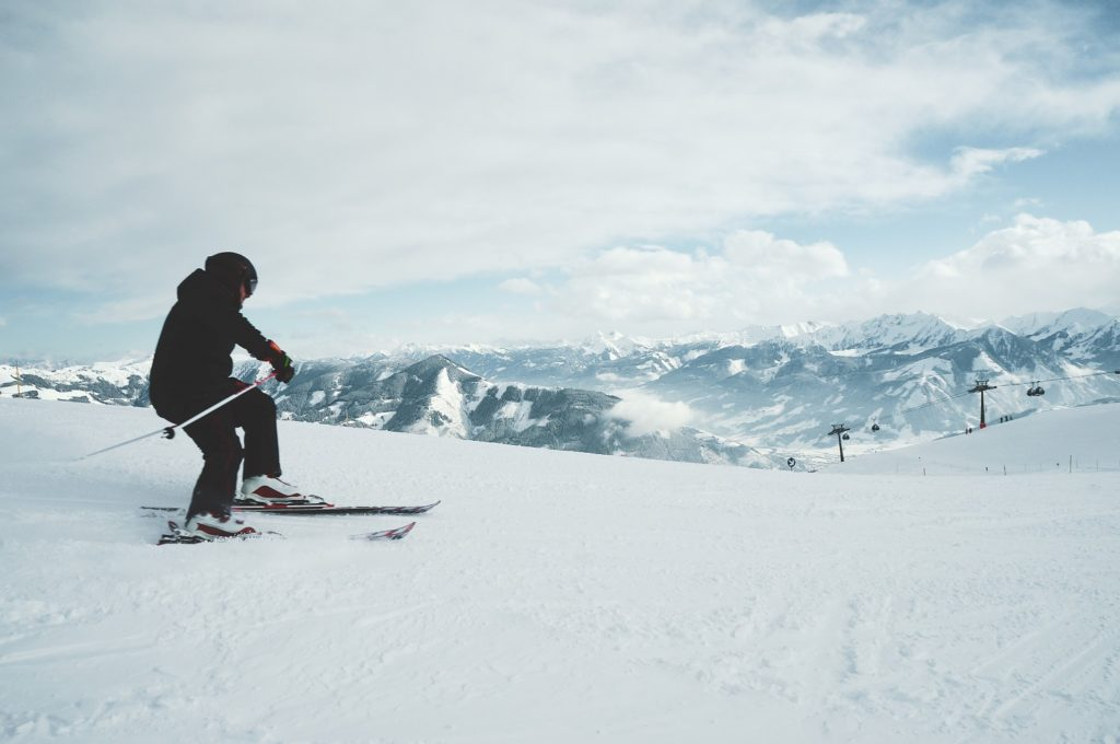 Male with a hearing aid skiing down mountain