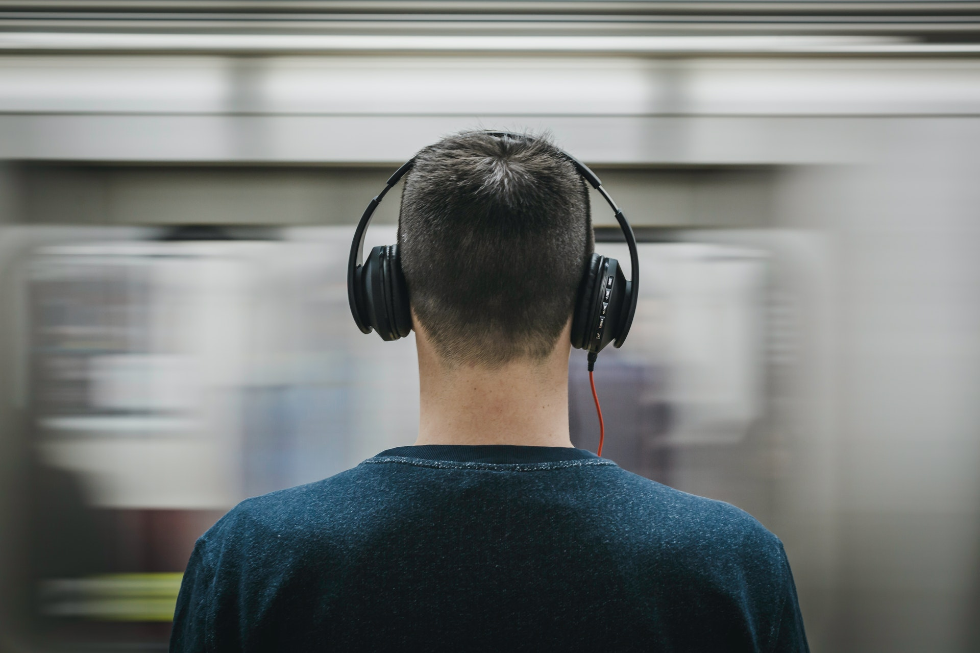 Man in public listening to loud music through his headphones, potentially causing noise-induced hearing loss