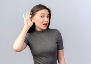 Woman having trouble hearing because of muffled hearing. Considering getting a hearing test