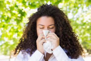 Woman outside sneezing with environmental allergies lead to hearing issues