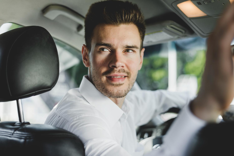 Close up of man reversing car, symbolizing the reversal of hearing loss