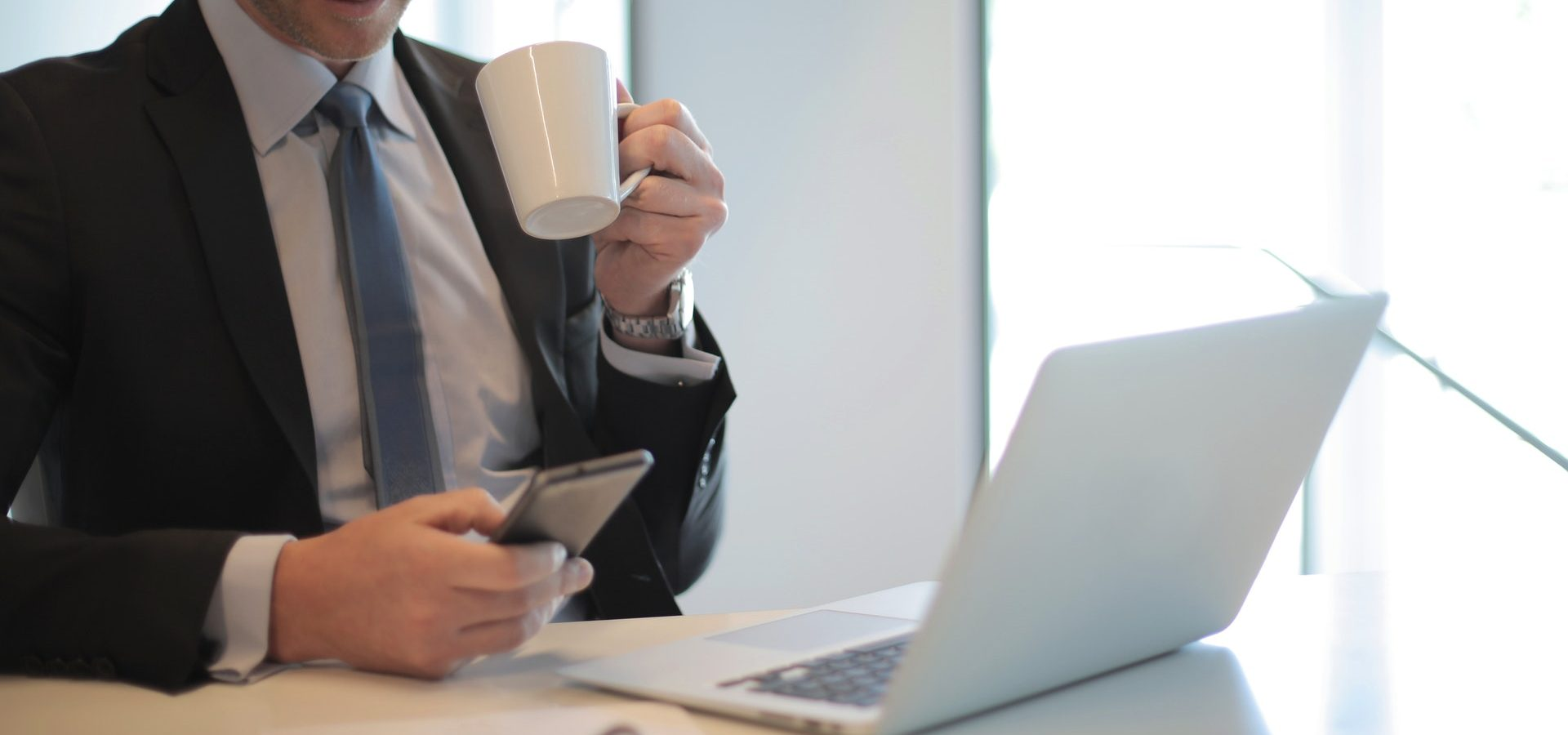 Man in black suit drinking coffee in front of laptop