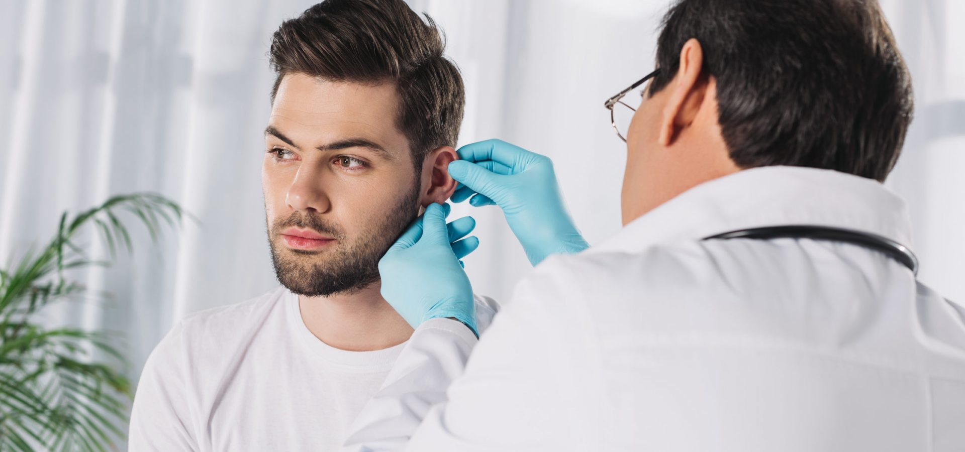 doctor examining male patient ear