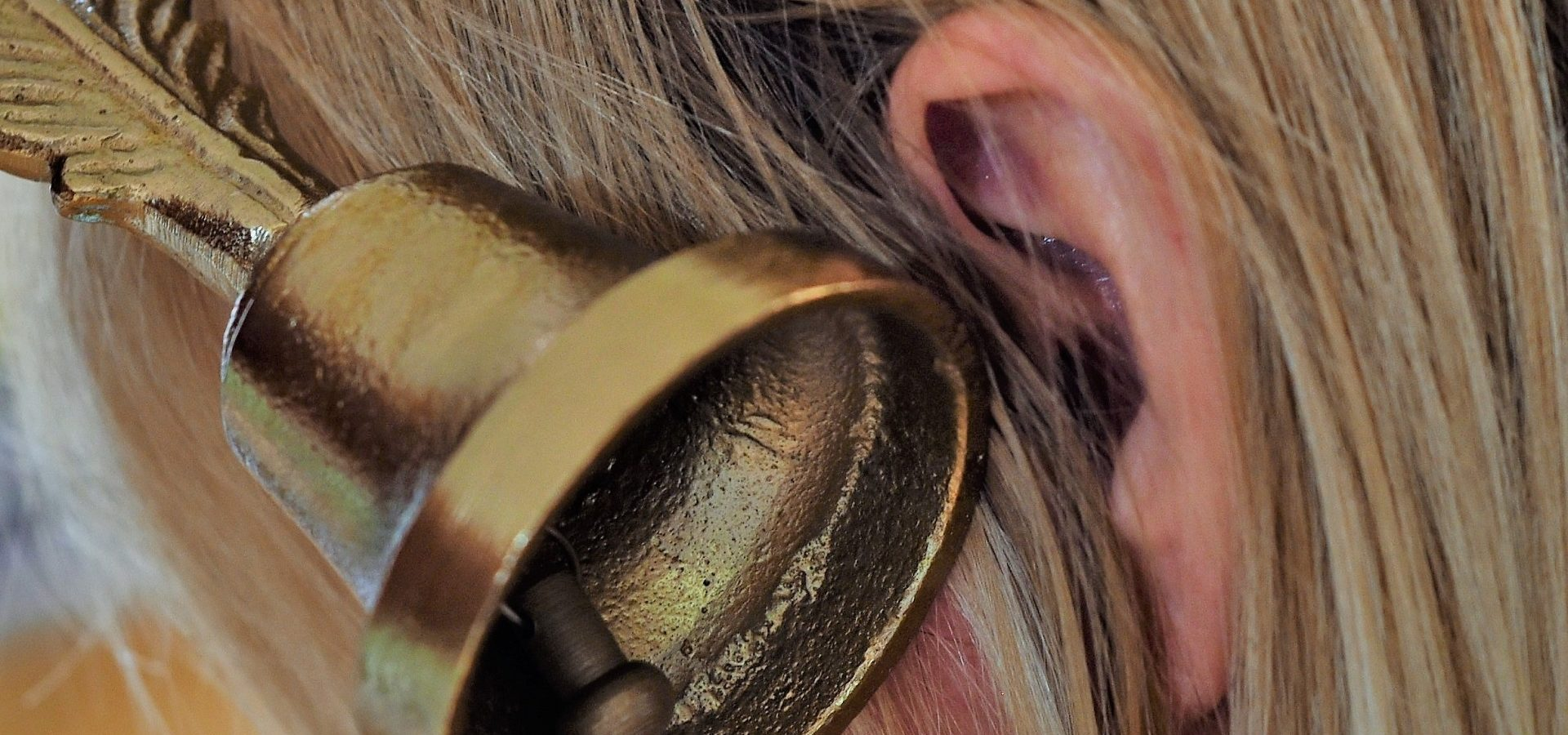 A bell placed next to a womans ear, representing the ringing sound associated with tinnitus