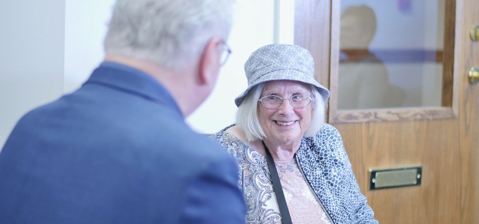 Senior woman talking with hearing aid practioner at an appointment