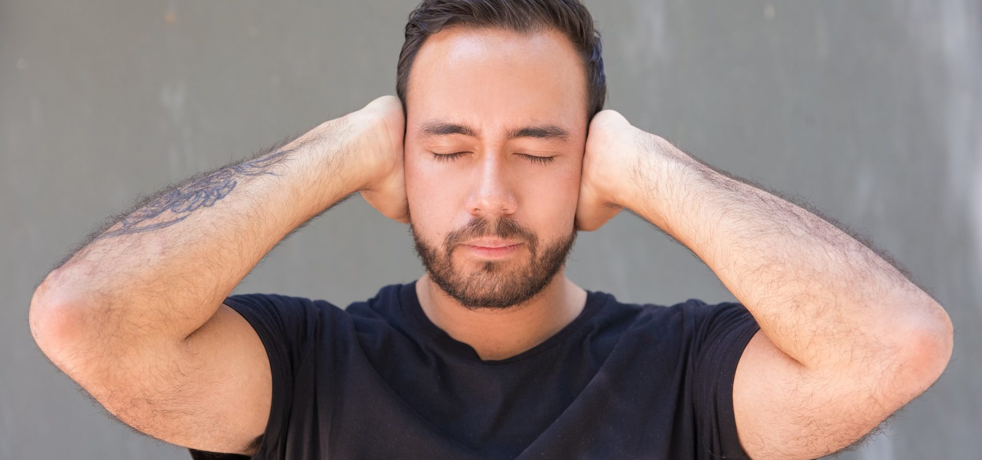 Bearded young man closing ears with hands. Young tattooed man in black t-shirt standing with closed eyes and closing ears on grey background. Silence concept