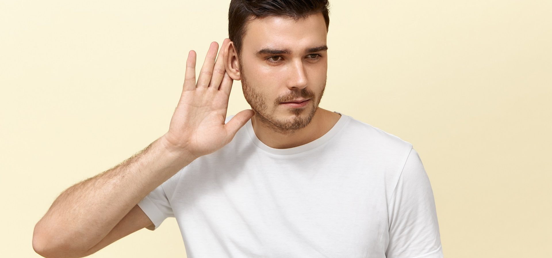 Young man holding his hand up to one ear, suffering from single-sided deafness