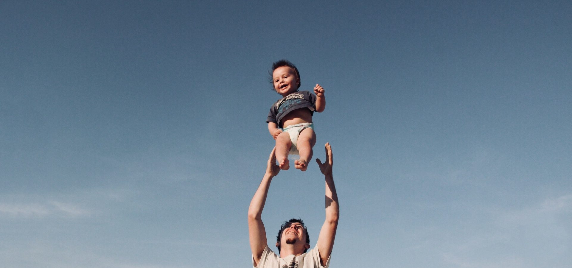 Dad raising his son in the air on a sunny day
