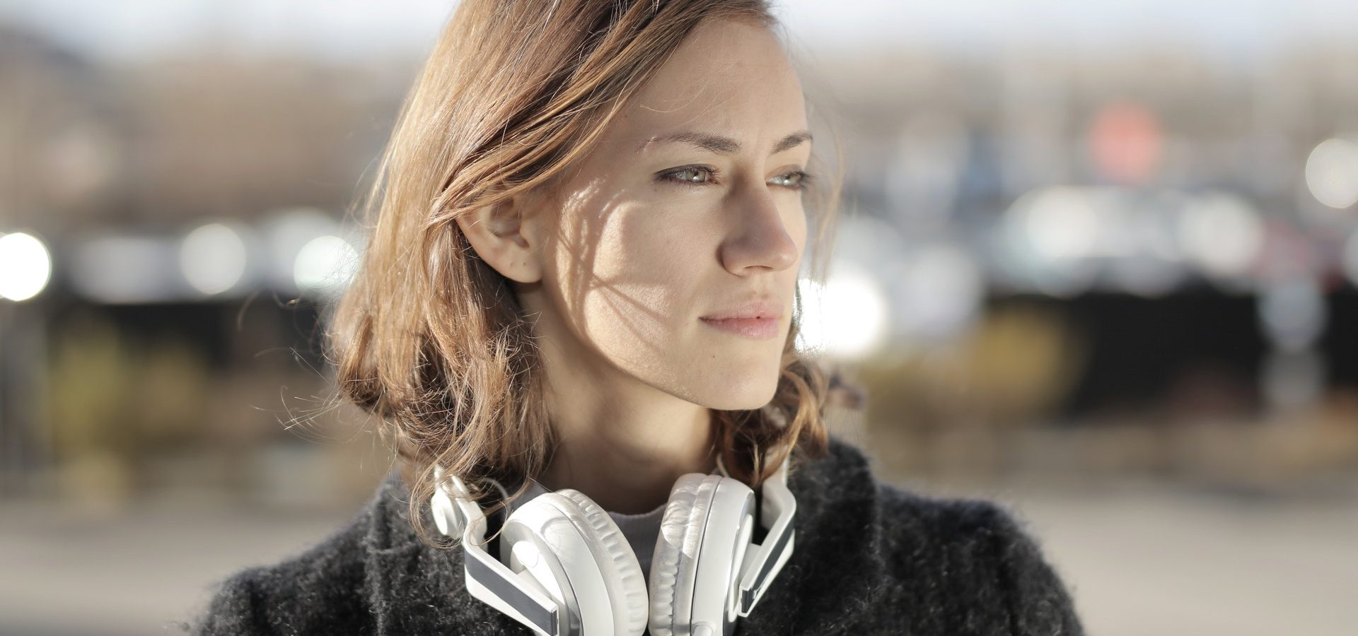 Woman with headphones around her neck outside